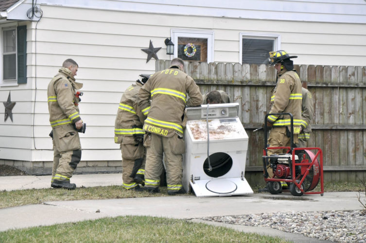 -Messenger photo by Peter Kaspari  Fort Dodge firefighters examine a dryer that was taken out of 1216 S. 25th St. after it caught fire Monday afternoon. According to Fort Dodge Fire Capt. Steve Teske, a woman who lived in the house smelled smoke coming from her basement and contacted the Fire Department. Firefighters went downstairs and found the dryer burning. Teske said the motor had burned out and ignited lint that was inside the dryer. Firefighters used pressurized water to put out the fire and removed the appliance from the home. Teske said there was some smoke in the basement which firefighters were able to air out. Nothing else inside the home was damaged.