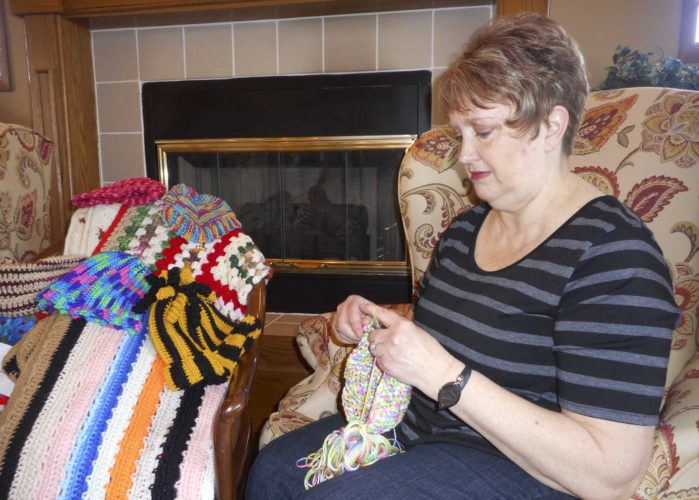 -Messenger photo by Karen Weld  Gretta Baumann, of Clarion, knits an afghan at The Meadows senior living center recently. The afghan is one of many items, along with the children's hats pictured above, that will be given away by the Knit Wits, a group Baumann started in 2007.