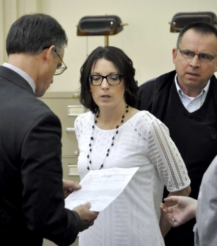 -Messenger photo by Peter Kaspari  Hillary Tyler, center, is handcuffed by Fort Dodge Police Detective Larry Hedlund, right, after her plea and sentencing hearing in Webster County District Court. Tyler's attorney, Neven Mulholland, is at left.