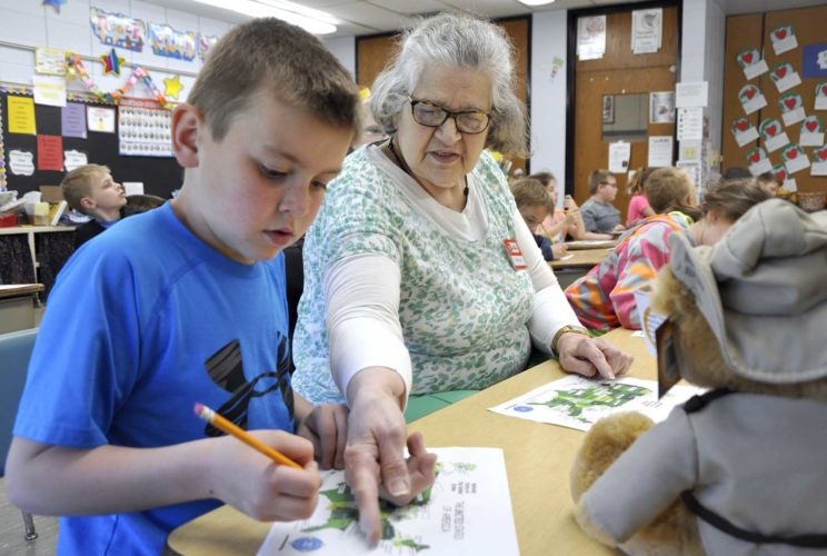-Messenger photo by Joe Sutter  Foster Grandma Vera Cerwick helps Aiden Armstrong and Haylee Scott, at right, with a geography exercise in Rita Engh's second grade class. Engh brings Cerwick into her class to help on a multitude of topics.