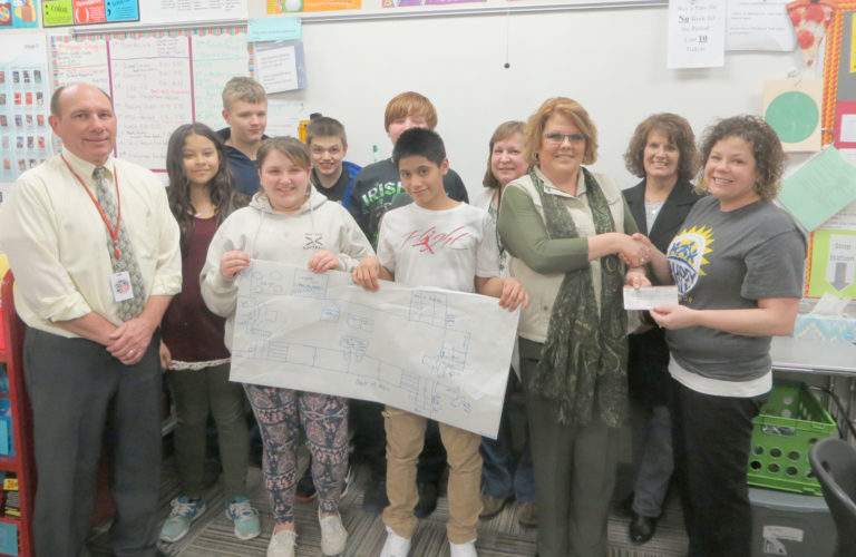 FDMS teacher Tina Gerdes received a $500 Buddy Grant from the Northwest Iowa Down Syndrome Society to create a trauma sensitive classroom for her students. The new classroom design will provide students a comfort zone where they can feel safe and build resilience to help them meet their academic goals with success.  Pictured from left are FDMS Principal Ed Birnbaum, Alexia Calles-Sheker, Bayleigh Shults, David Ramos, Gerdes  and Tara Rochleau, Northwest Iowa Down Syndrome Society. In back from left are Koltin Lowe, Gavin Riley, Ben Crouse, Judi Smith and Liesl Vaughan.