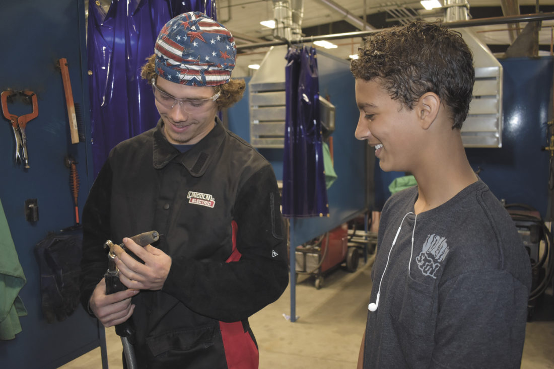 -Messenger photo by Chad Thompson  Ozzy Pattison, 18, a senior at Fort Dodge Senior High, left, shows Izaih Clark, 16, a sophmore at FDSH, a welding gun inside one of the welding bays at the North Central Career Academy in Eagle Grove Monday morning. Clark is interested in the welding program offered through the academy. He can begin taking those classes his junior year.