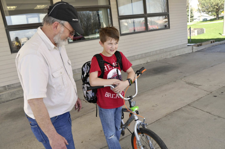 -Messenger photo by Joe Sutter  Doug Bargfrede, who is with the Dodger Cyclists club, talks with Tavian Klass, a fifth-grader, about the lights on his bike outside of Icky's after school program Monday. The club was there to hand out red and white lights for the front and back of bikes to improve visibility and make kids safer. The Dodger Cyclists club has been doing handouts at schools throughout Fort Dodge. Icky's is a place for kids from fifth to 12th grade, although most of the students come from the Fort Dodge Middle School, said Director Caleb Carlson. The center is run by a number of churches working together and provides a place for kids after school.