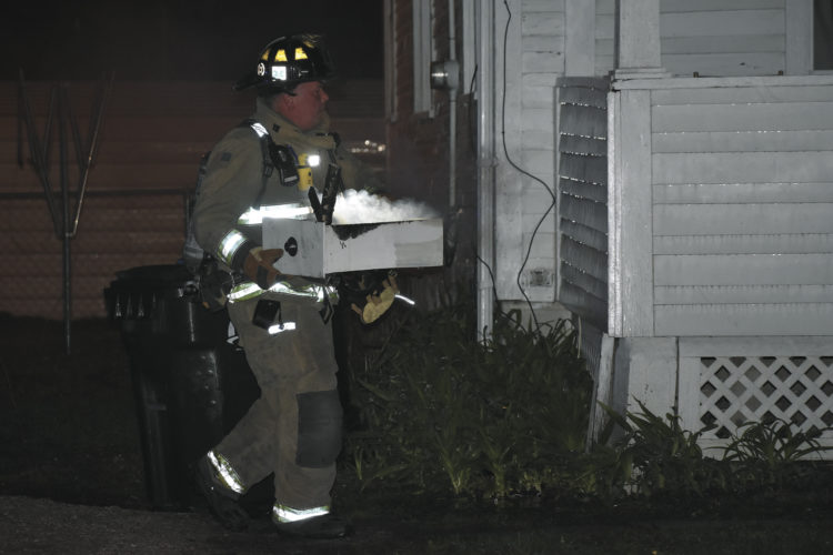 -Messenger photo by Chad Thompson  A Fort Dodge firefighter carries out a smoking cabinet drawer from a house that caught fire Wednesday night. The fire was contained to the kitchen of the house, located at 846 S 24th St., according to Capt. Steve Hergenreter, of the Fort Dodge Fire Department. Two people were reportedly inside the house at the time of the fire, but escaped uninjured, according to Hergenreter. The two people were treated on scene, Hergenreter said. A cause was not determined Wednesday night.