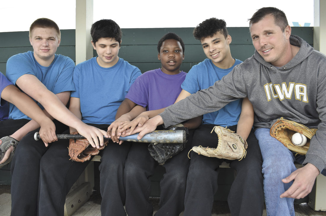 -Messenger photo by Chad Thompson  Members of the Rabiner Treatment Center baseball team place their hands as one on a baseball bat inside the dugout at the Rabiner baseball field Tuesday. Pictured from left to right: Matthew Langel, 16, Ismael Torres, 13,  Fletcher Jackson, 13, Emilio Ratchbun, 15, and Head Coach Andy Daniel.