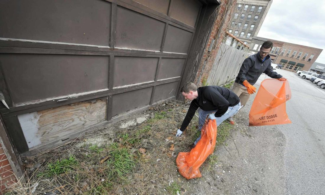 -Messenger photo by Hans Madsen  Luke Huggins, at left, along with Austyn Wolfe, both with McClure Engineering, work on picking up garbage in an alley along Central Avenue between north Sixth and Seventh streets Thursday afternoon during the annual FOD Walk.