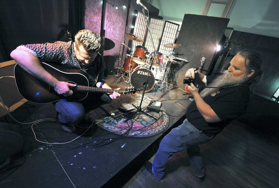 -Messenger photo by Hans Madsen  Artist Roger Feldhans, of Pomeroy, at right, records a picture of musician Chad Elliott tuning up before a recent show at the Prairie Blue Creative Arts Center in Jefferson. Feldhans' photographs of musicians have been included as cover art on many of their albums including ones by Elliott.