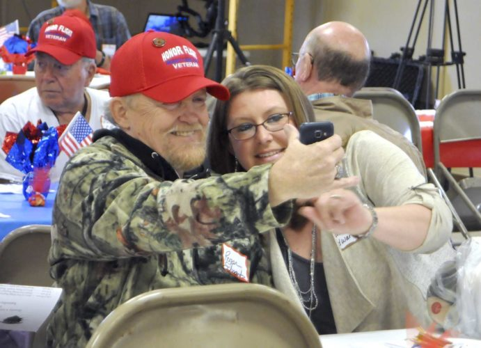 -Messenger photo by Peter Kaspari  Army Veteran Roger Edwards, left, of Emmetsburg, takes a selfie with his daughter, Kasey Edwards, at the Brushy Creek Area Honor Flight banquet Wednesday evening.