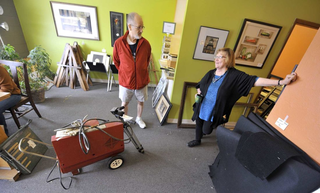 -Messenger photo by Hans Madsen  Loren Miller, of Fort Dodge, visits with Buckroyd Studio owner Maureen Powers Saturday morning after stopping by to shop and chat at her garage sale of studio items. Miller purchased a small paper cutter.