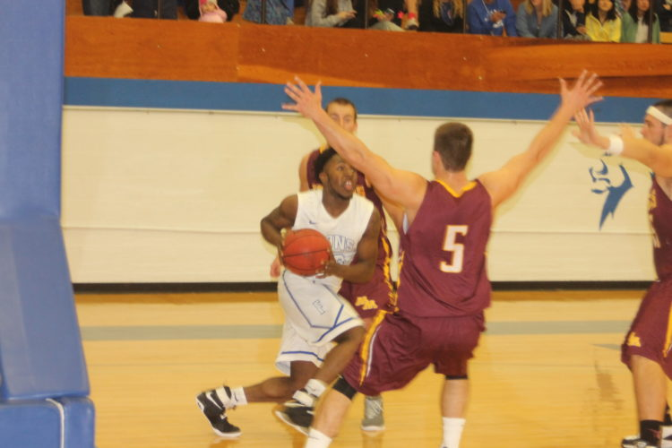Paul Peterson photo Finlandia's Brandon Robinson runs into a Minnesota Morris defender in Friday's game at Paavo Nurmi Gym.