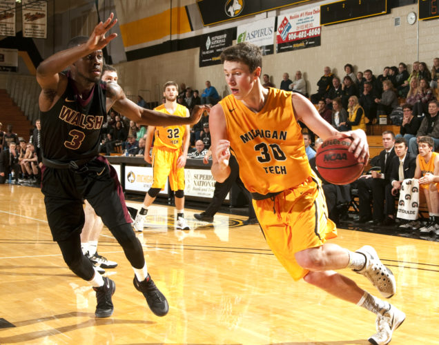 David Archambeau/Daily Mining Gazette Michigan Tech's Kyle Monroe drives against Walsh's Jamel Moore Saturday at the Wood Gym. Monroe scored a career-high 39 points in Tech's 92-89 win.