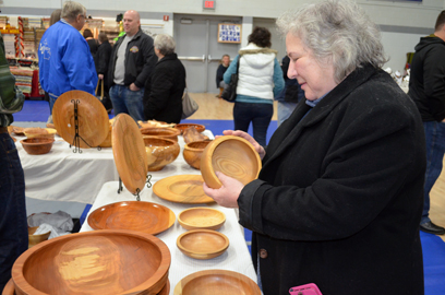 Kurt Hauglie/Daily Mining Gazette Linda Lohman of Houghton looks over some wooden bowls Saturday made by artist David Payant of Marquette at the Copper Country Community Arts Center 40th annual Poor Artists sale at the Calumet High School gymnasium.