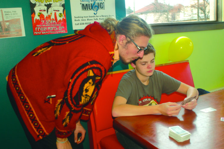 Marquette Senior High School student Perry Truscon, 17, left, helps fellow Marquette student Zane Farnsworth, 15,  with his Star Fluxx game Wednesday at the opening of the new Teen Zone at the Peter White Public Library. Kids age 13-19 now have a place of their own to study, play games and other activities. (Journal photo by Christie Bleck)