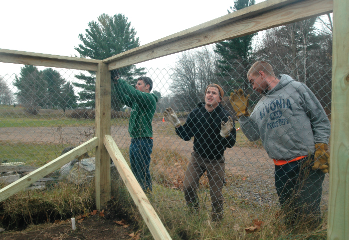 From left, Northern Michigan University construction management students Mitch Hanson, James Eickhoff and Daniel Hunter rebuild the fence around the community garden at Park Cemetery in Marquette. The garden, along with the other Marquette community garden on Presque Isle, allows people to grow their own fruits and vegetables. (Journal photo by Christie Bleck)