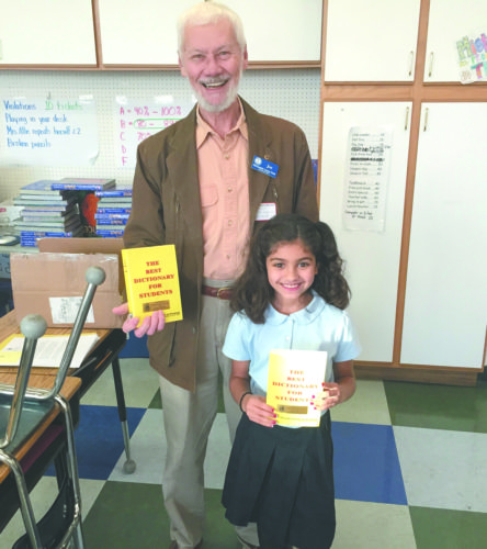 For the seventh straight year, the Marquette Lions Club has provided dictionaries to the third graders in Marquette and Marquette Township. The Dictionary Project aims to promote reading and education for our youth. Pictured are Reyna Ghiardi, third grader at Father Marquette Elementary School and Lions Member, Joe Baczkowski.