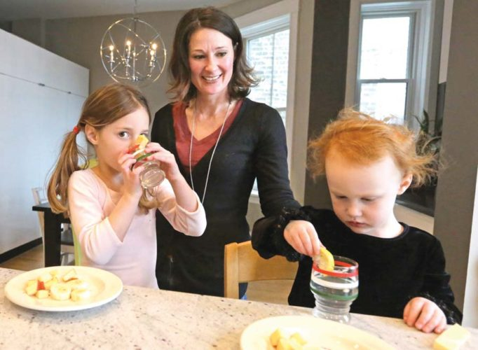 Kathy Burnett prepares a snack for her daughters Claudia, center, and Sabina right, after their gymnastics class  Jan. 29, 2015, in Chicago. Burnett says she tries to feed her girls healthy, natural foods rather than commercial packaged products. A study by the federal Centers for Disease Control and Prevention found that many packaged foods and snacks marketed for toddlers contain too much salt and sugar and could potentially contribute to childhood obesity and high blood pressure. (AP photo/M. Spencer Green)