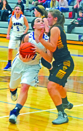 Gladstone's Taylor Hunter drives to the basket on Gwinn's Brenna Bruce in Friday's game. (Escanaba Daily Press photo by Mike Mattson)
