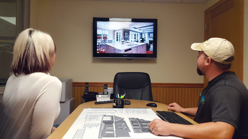 Chris Pesola shows a customer how their new home will look using Wausau Homes of Marquette's 3D software. The company uses this to help customers visualize their home before the building process evens stats.