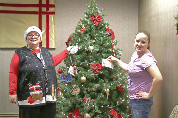 Cheryl Dupras, left, and Tonya Croschere, right, add their ornaments to the Christmas tree during the Trim the Tree event at the Holiday Inn of Marquette. (Journal photo by Rachel Oakley)