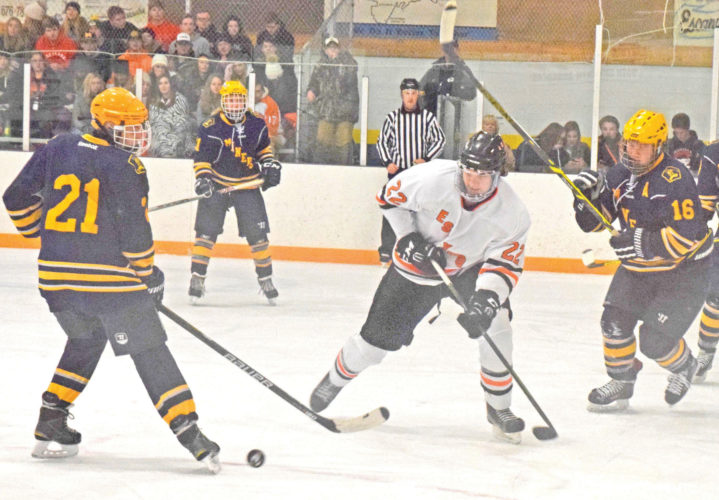 Negaunee's Anthony Hammermaster, left, and Jacob Paquet, right, defend against Escanaba's Colton Hayes during their high school hockey game held at the Eskymos' rink on Monday. (Escanaba Daily Press photo by Mike Mattson)