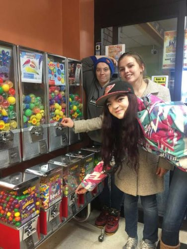 From left, students Savannah Fortin, Morgan Madosh and Sky Boyle feeds coins into the kids' toy machines at a local grocery store. Other students raked leaves, shoveled snow, carried groceries at two stores and handed out flowers. The rest of the school conducted a can drive to raise money for their canoe trip down the AuTrain River. (Photos courtesy of Cindy DePetro, Marquette Alternative High School)