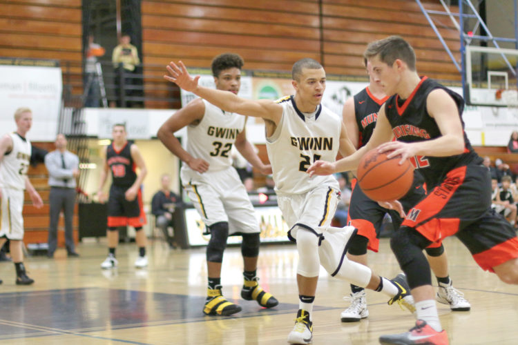 Munising's Cade Contreras, right, dribbles toward the lane as Gwinn's Jalen Skinner, center, and Tucker Taylor defend Tuesday night at the Modeltowners' gym. (Journal photo by Rachel Oakley)