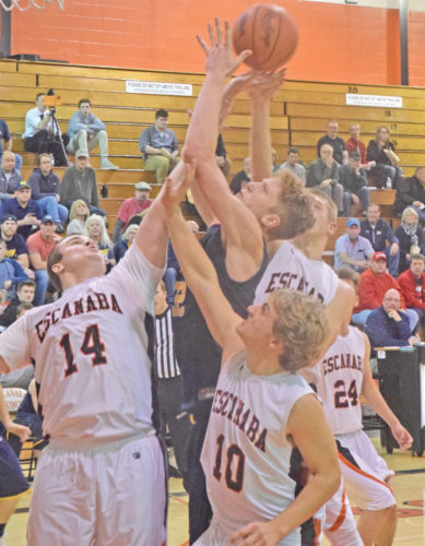 Negaunee's Trent Bell, center in dark uniform, is sandwiched by Escanaba defenders, from left, Dalton Deneau, C.J. Barron and Tyler Willette while battling for a rebound Tuesday at Escanaba. (Escanaba Daily Press photo by Mike Mattson)