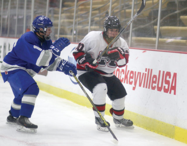 Marquette's Tanner Phillips, right, keeps an eye on the puck with Calumet's Trevor Salata closing in Tuesday night at Lakeview Arena in Marquette. (Journal photo by Rachel Oakley)