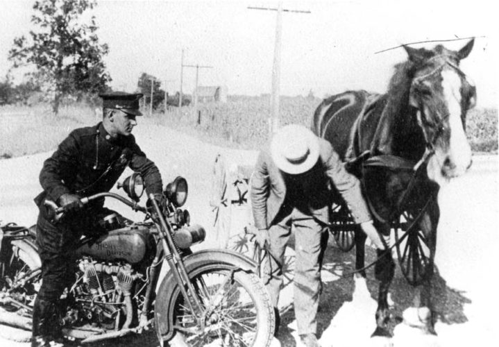 A Michigan State Police trooper on a motorcycle stops to offer assistance, circa 1920s. (Photo courtesy of the Marquette Regional History Center)