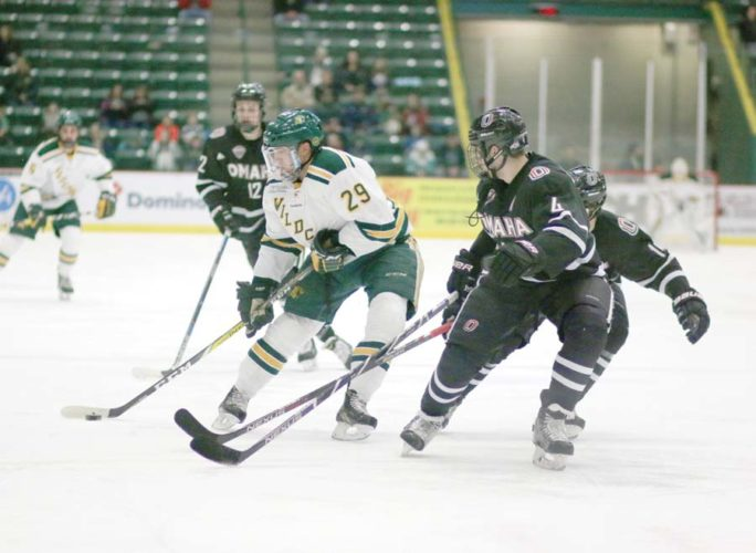 Northern Michigan University forward Robbie Payne, center, guides the puck past Nebraska-Omaha defensemen Luc Snuggard, right, and Teemu Pulkkinen, right hidden, on Nov. 26, 2016, at the Berry Events Center in Marquette. (Journal photo by Rachel Oakley)