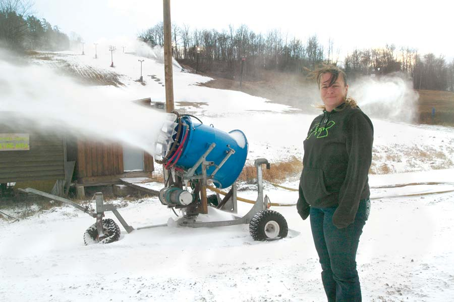 Jesie Melchiori, general manager at Marquette Mountain, said the  facility will open Saturday.  Behind Melchiori is one of the snow guns in operation on the mountain. (Journal photo by Christie Bleck)
