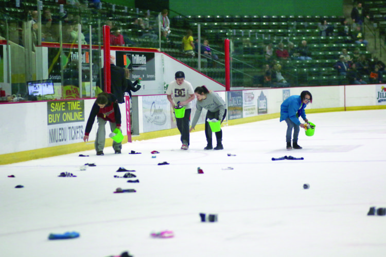 Students of Vandenboom Alternative High School pick up socks that have been donated to their Rock the Socks! event during the Northern Michigan University versus University of Alabama Huntsville game at the Berry Events Center in Marquette on Friday night, Dec. 10, 2016. (Journal photo by Rachel Oakley)