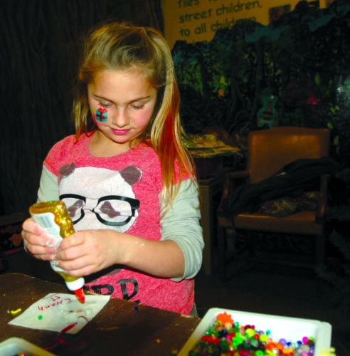 Nevaeh Hanson, 9, of Ishpeming, creates a Christmas tree ornament during the Second Thursday Series event at the Upper Peninsula ChildrenÕs Museum. The focus Thursday was the tale, ÒThe Polar Express.Ó (Journal photo by Christie Bleck)