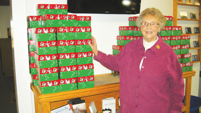Submitted Photo Lois A. Kankovsky stands by a shelf full of shoe boxes for Operation Christmas Child, a project of Samaritan's Purse.