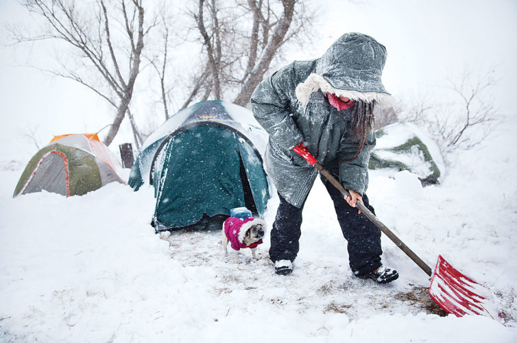 AP Photo Loretta Reddog, of Placerville, Calif., shovels a walkway to her tent while followed by her dog Gurdee Bean at the Oceti Sakowin camp where people have gathered to protest the Dakota Access oil pipeline in Cannon Ball.