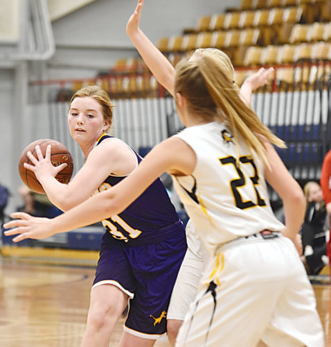 Garrick Hodge/MDN  Bishop Ryan's McKinlee Harmon (31) looks for a passing lane during a girls high school basketball game on Friday in Minot.