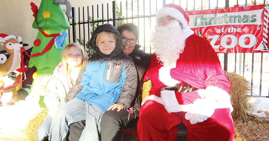 "Allan Blanks/MDN  From left to right, Jerra Carroll, Jaxson Carroll and Cindy Jenson sit beside Santa Claus during the annual ""Christmas At the Zoo"" held Saturday afternoon."
