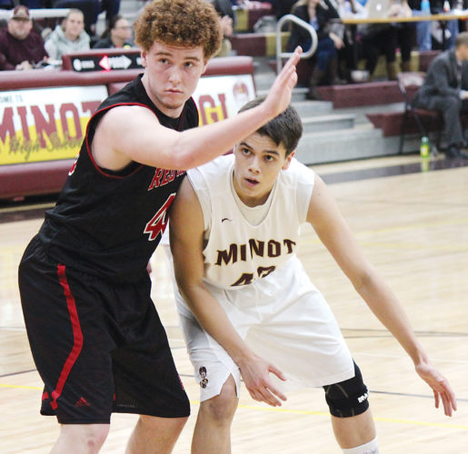 Alex Eisen/MDN Magi center Max Olthoff (42) fights for position on an inbounds play Saturday against Grand Forks Red River at Minot High School.