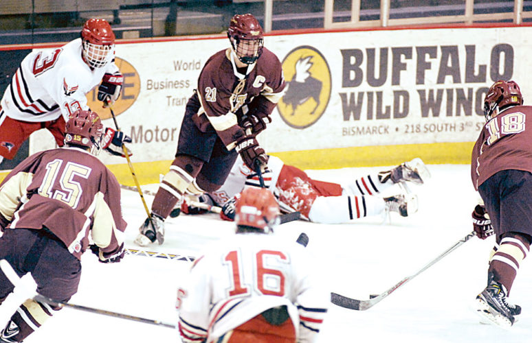 Photo courtesy of the Bismarck Tribune.  Minot High's Easton Bennett (21) weaves through the traffic of Century players to pass the puck to teammate Jake Viall (18) in the second period of Thursday night's game in Bismarck. Century won 6-5.