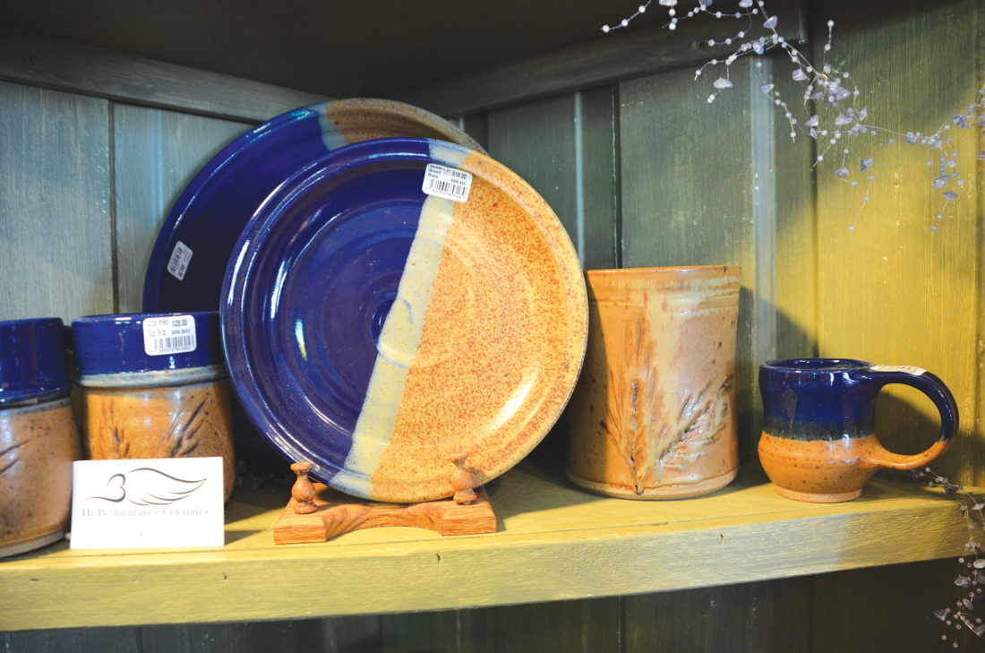 Eloise Ogden/MDN Pottery by Jim Bailey of Minot, including his signature piece with embedded wheat, is displayed on a shelf in Home Sweet Home.