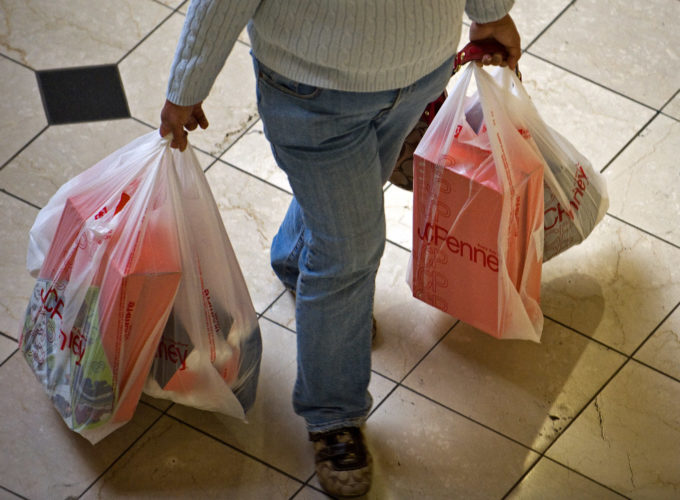 A shopper at the Brea Mall in Brea, Calif., carries bags full of packages. Amid the holiday decorations and cheerful ads, splurging is not an option for many Americans struggling to get by. (Michael Goulding/The Orange County Register via AP, File)