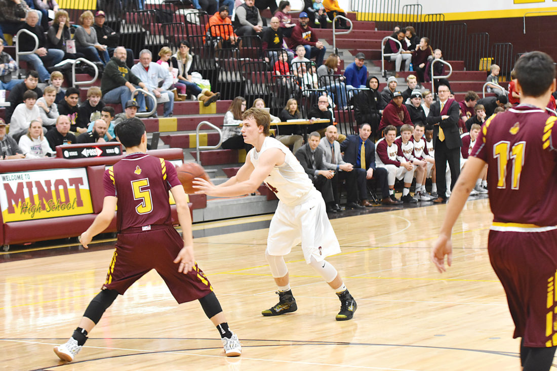 Garrick Hodge/MDN Minot High's Peyton  Lamoureux (24) surveys the passing options at the top of the key during a boys high school basketball game Tuesday.