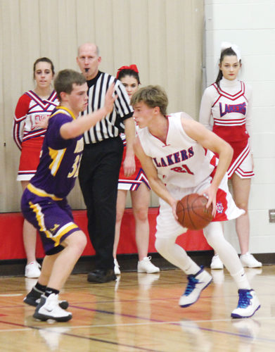 Alex Eisen/MDN DL-B junior Joshua Knutson (21) squares up his defender in a Class B boys basketball game played Friday night in Burlington. The Lakers won 77-57.
