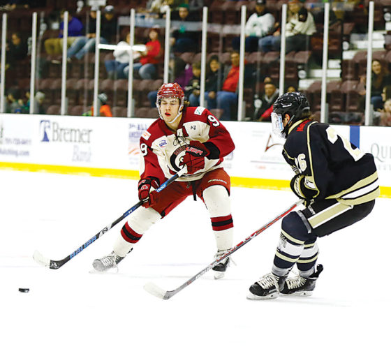 Steve Silseth/Special to The Minot Daily News  Minot's Zack Bross (9) looks for a shot while Bismarck's Michael Mahan (26) defends him during a junior league hockey game Saturday at Maysa Arena.