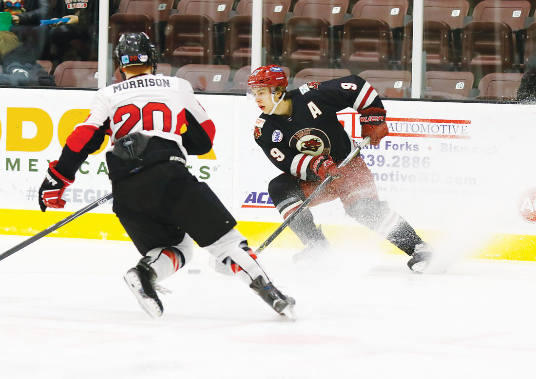 Steve Silseth/Special to The Minot Daily News  Minot Minotauros forward Zack Bross (9) looks to move the puck while attacking while Minot State's Carey Morrison (20) defends during an exhibition game Monday at Maysa Arena.