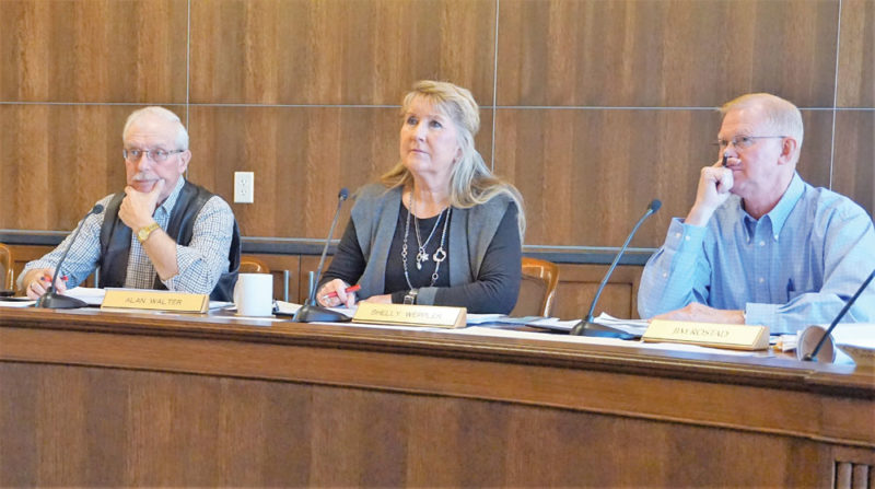 Jill Schramm/MDN Ward County Commissioners Alan Walter, Shelly Weppler and Jim Rostad listen to a presentation by a state weather modification official Tuesday.