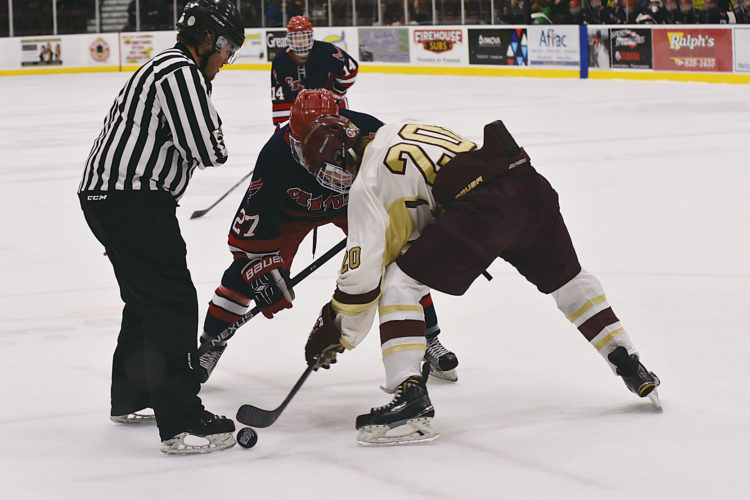 Garrick Hodge/MDN Minot's Kyler Stenberg (20) takes a face off against Bismarck Century Tuesday at Maysa Arena.