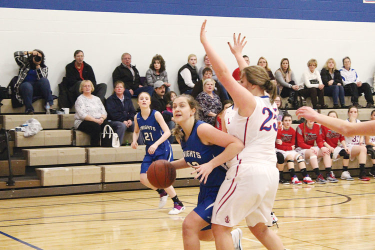 Mark Jones/MDN Our Redeemer's Christian School sophomore Cara Steede drives to the basket past the defense of Des Lacs-Burlington senior McKenzie Munday during the second period of Tuesday night's Class B District 12 contest in Burlington. DL-B won the game 68-49.
