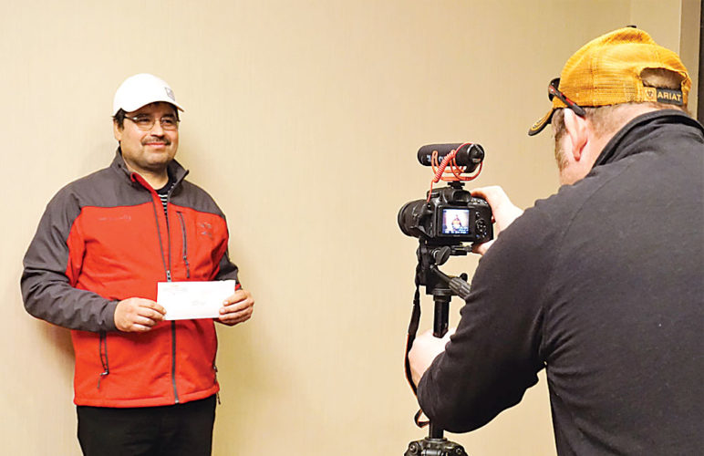 Jill Schramm/MDN A former WCE Oil Field Services employee holds his check as he prepares to record his thanks to an anonymous donor at a labor union event in Minot Monday.