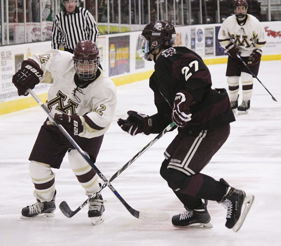 Alex Eisen/MDN Minot High's Joey Viall and Bismarck's Chase Fuhrman jostle for position on the ice Thursday night in a West Region hockey game played at Maysa Arena.